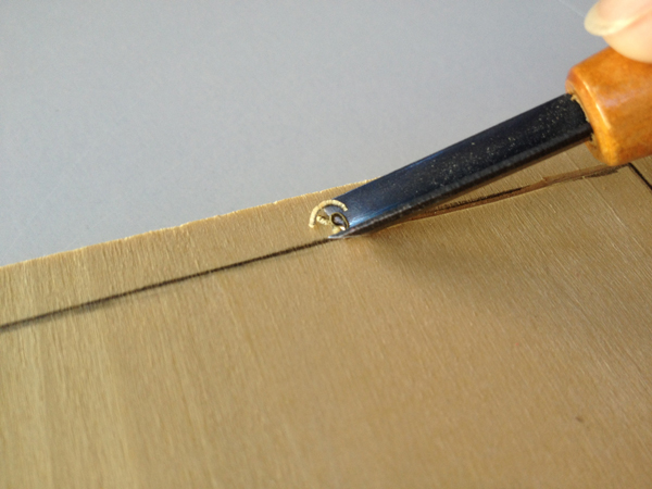 3. Start Carving - Step 1 - Use the V-shaped gouge to carve against the grain.