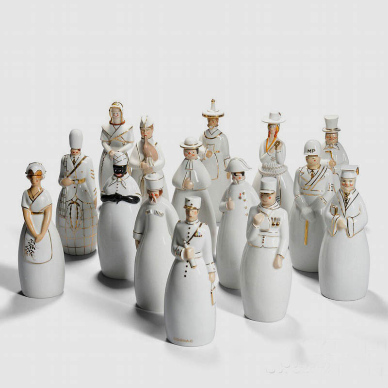 Fifteen Robj Liqueur Decanters, Glazed Ceramic, France, 20th Century, The anthropomorphic containers in white glaze with gold highlights represent: a kilted Scotsman, French soldier, African woman, military policeman, Russian peasant, bagpiper, priest, gentleman in a top hat, general with field telescope, Napoleon Bonaparte, professor, and four women in traditional folk dress representing Champagne, Brittany, Bresse, and Mont Cenis, marked with various Robj stamps, some also marked Limoges, approx. ht. 11 in.